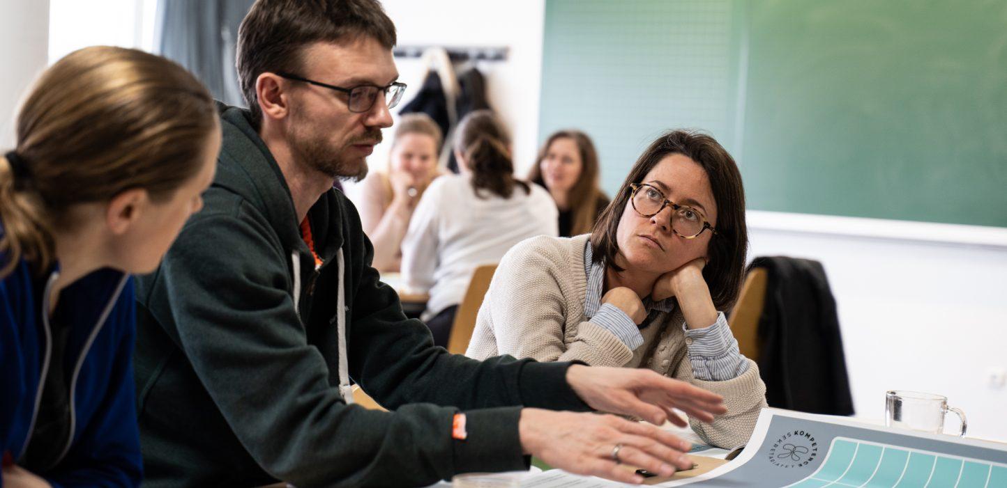 En mand sidder imellem to kvinder der kigger på ham. Foran ham er en dialogplade fra Kompetencedialogen.