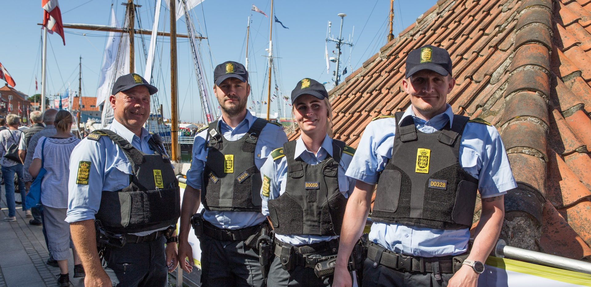 Fire betjente med veste og kasketter, står og smiler i solen ved havnen i Allinge.