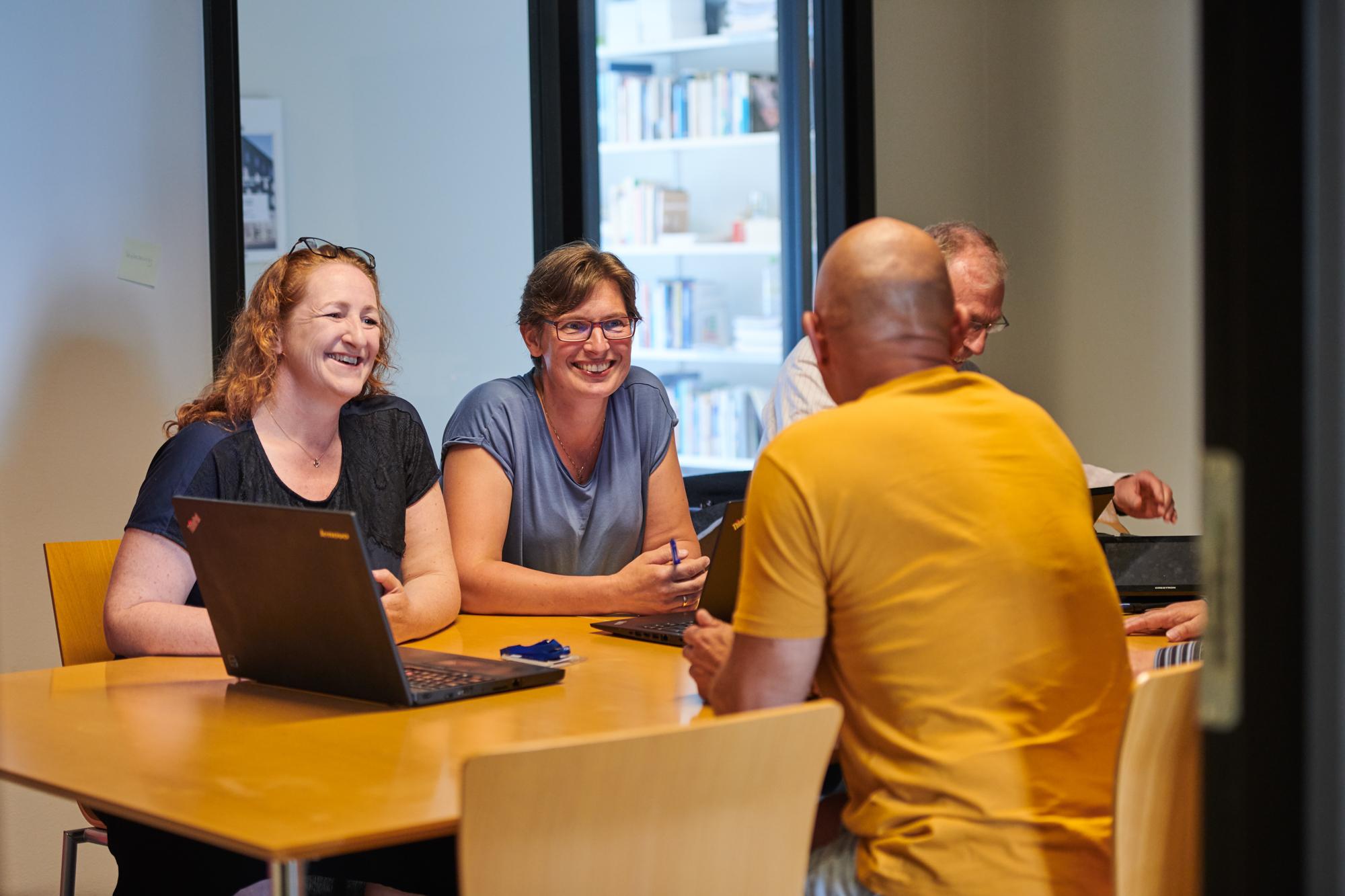 Fire personer om et bord. Mand med rykken mod beskuren har en gul t-shirt på. De andre smiler og kigger på ham. Der er en bærbar pc på bordet.
