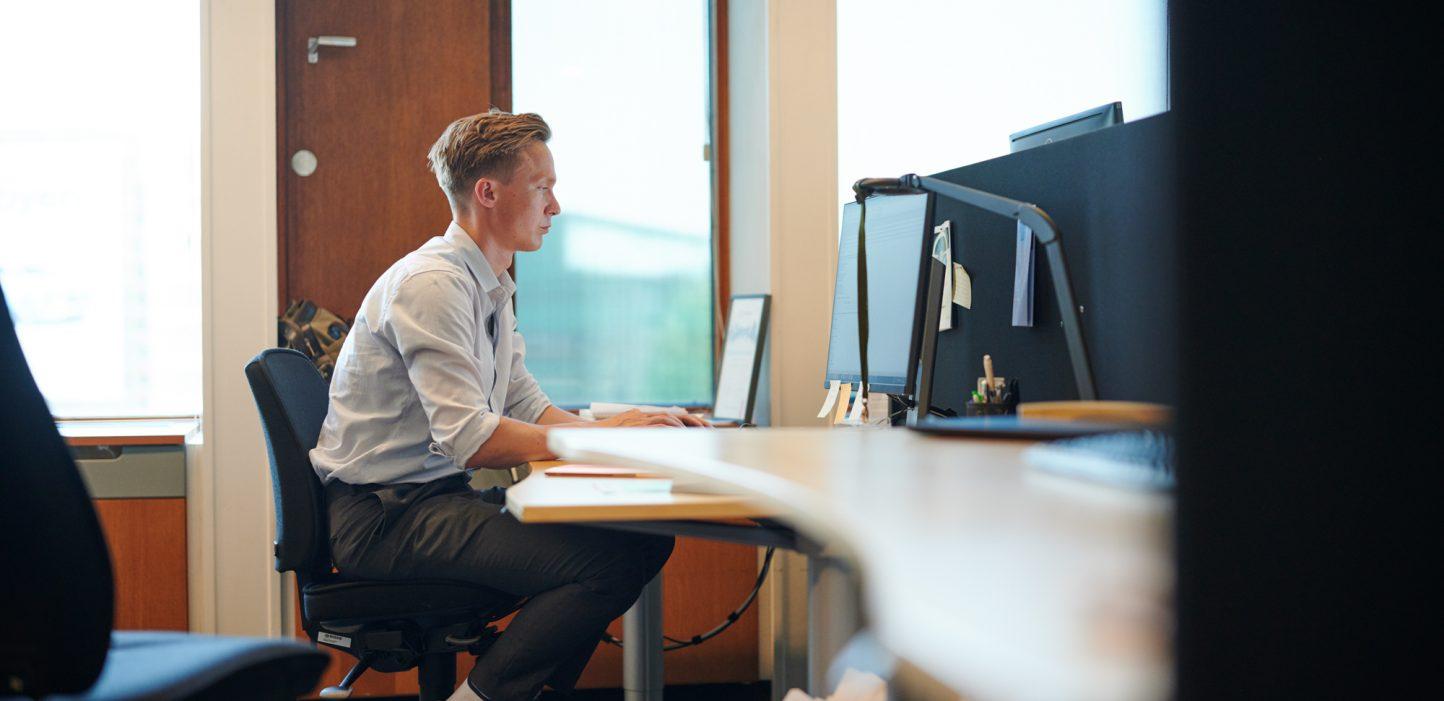Mand sidder ved skrivebord og kigger på computerskærm.