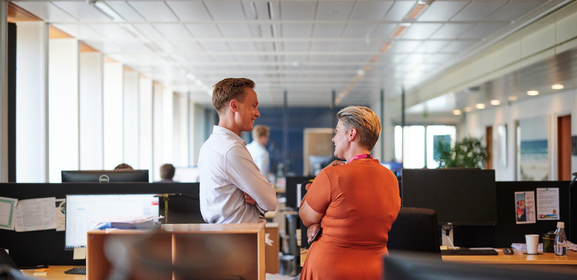 Mand og kvinde taler sammen i en arbejdsplads' fællesrum, hvor der er mange computere.