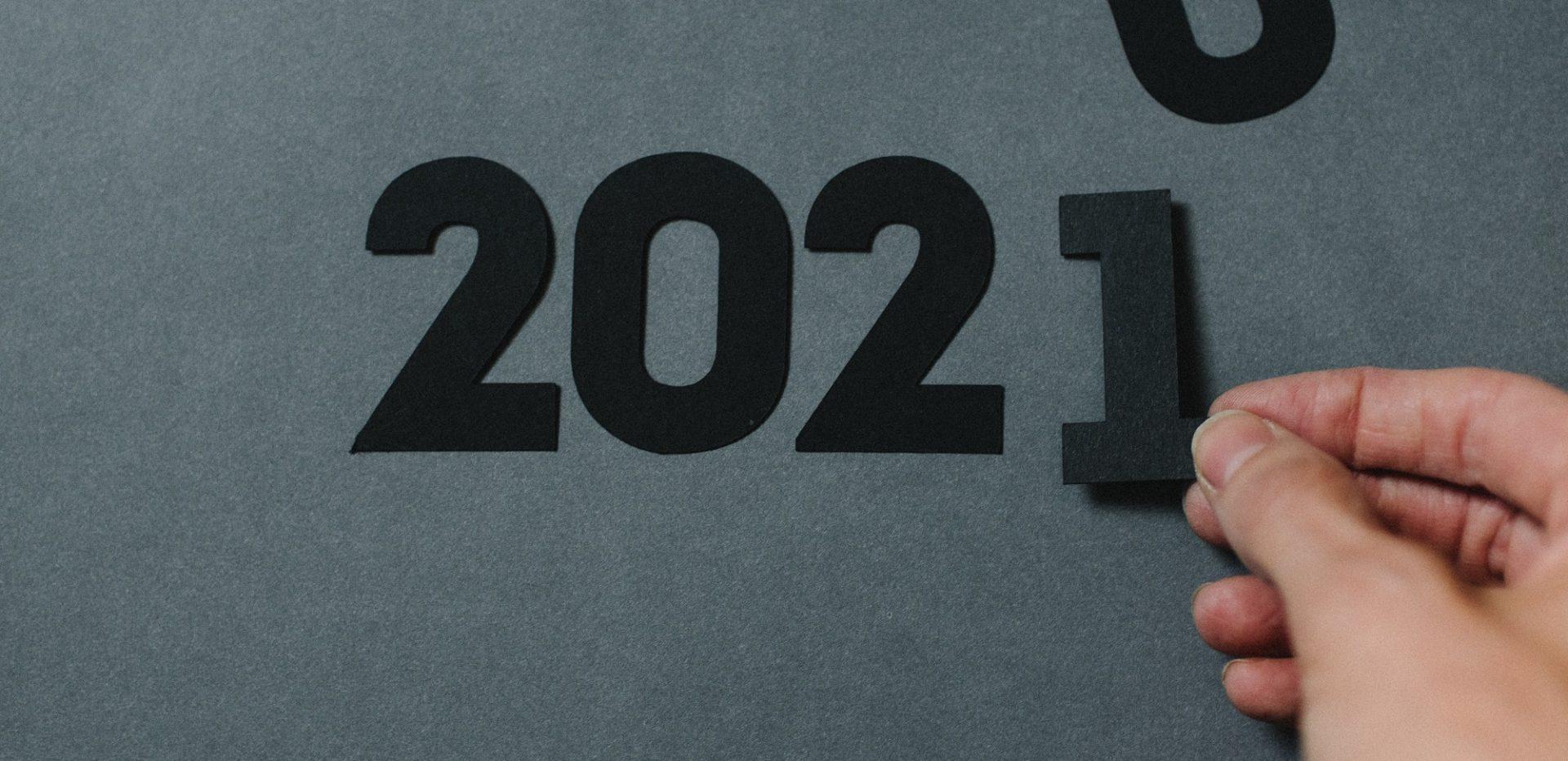 En hånd indsætter et 1-tal til årstallet 2021