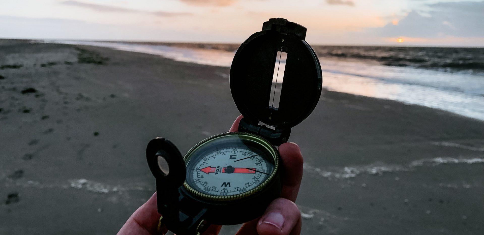Kompas holdes i hånden på en strand