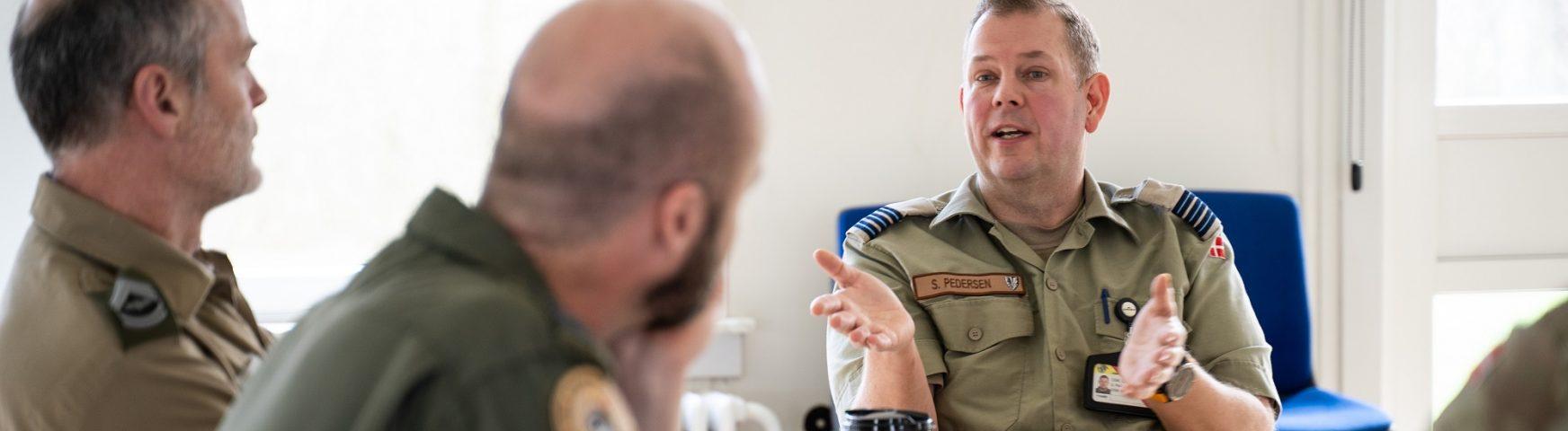 Tre soldater taler sammen ved bord
